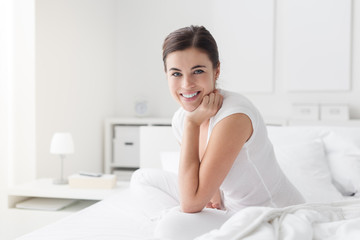 Happy woman posing on the bed