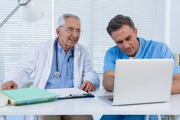 Surgeon and doctor discussing over laptop