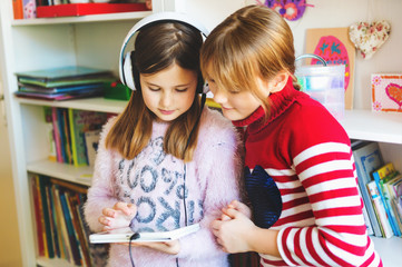 Two cute little girls playing on digital tablet pc