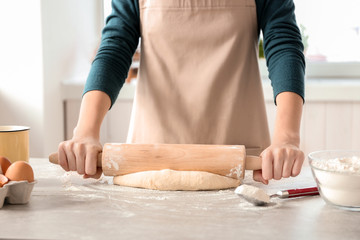Woman preparing dough on table at kitchen