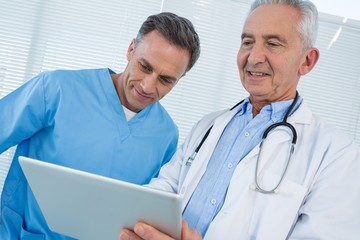 Surgeon and doctor discussing over digital tablet