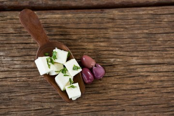 Cheese cubes garnished with herbs and olives on wooden spoon