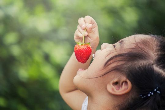 Beautiful little smiling girl eating strawberries in garden