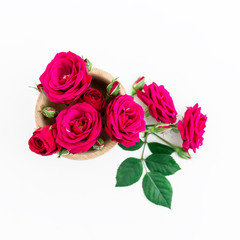Valentines Day background. Red roses and green leaves on white background. Flat lay, top view. Valentine's background