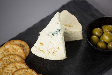 Pieces of cheese with biscuits and olives on slate plate