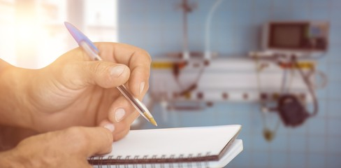 Composite image of close up of man writing in notepad