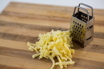 Grated cheese and grater on wooden cutting board