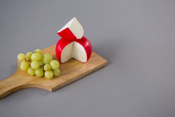 Gouda cheese with grapes on chopping board