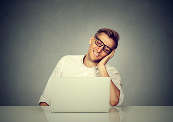Satisfied with work done man sitting in front of laptop computer