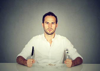 Man with fork and knife sitting at table with empty plate