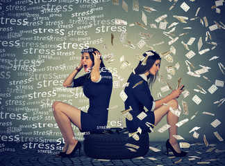 Women sitting on tire stressed and successful under money rain