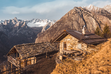 Old stone chalets with mountains in the background