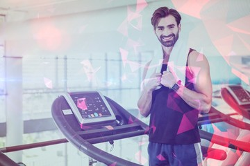 Portriat of smiling man standing on treadmill