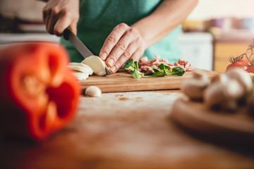 Woman slicing mozzarella cheese