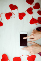 Woman holding smartphone over love heart background
