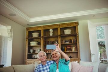 Senior couple taking a selfie on mobile phone in living room