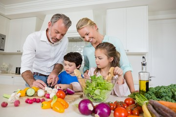 Parents assisting kids in chopping vegetable
