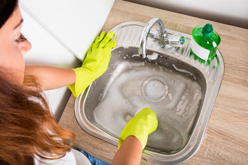 High Angle View Of Woman Cleaning The Sink
