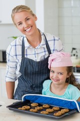 mother and daughter holding tray of baked cookies