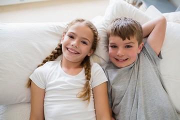 Siblings relaxing on bed in bedroom