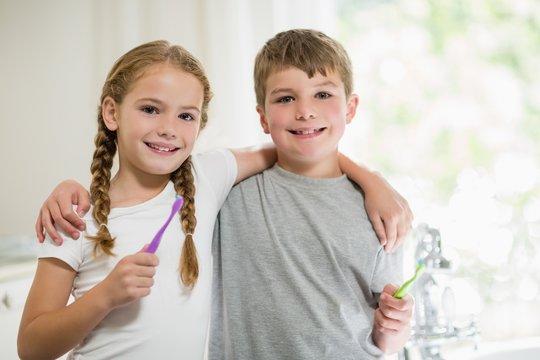Siblings brushing teeth in bathroom