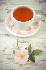 Vintage photo, Cup of tea and wild rose flower on old rustic wooden background