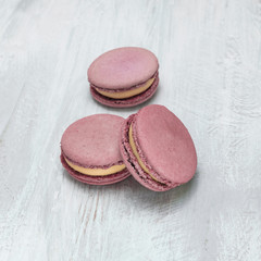 Pink macarons on pale whitewashed board with copyspace