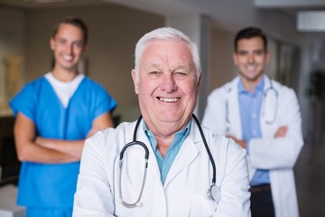 Portrait of smiling doctors standing with arms crossed