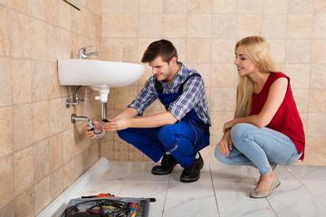 Young Male Plumber Repairing Sink In Bathroom