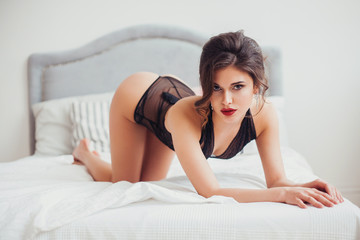 Beautiful sexy woman wearing seductive black lingerie posing in bedroom