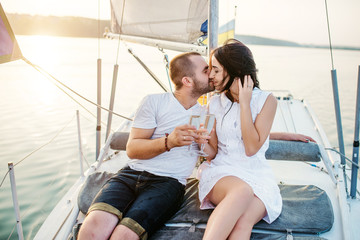 Young beautiful married couple in love at the yacht on vacation.