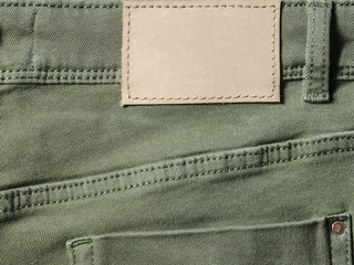 Green denim textile for background back closeup with leather label