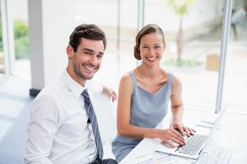 Business executives sitting with laptop