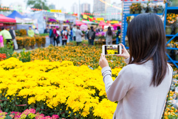 Woman taking photo on flower in flower market