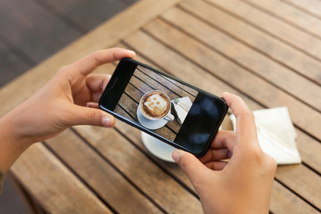 close-up hand holding phone mobile taking photo coffee on table