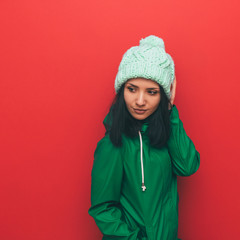 Hipster brunette lady in hat and green clothing on red background. Winter fashion.