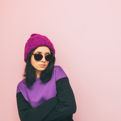 Lady is standing in winter clothing and round sunglasses. purple trendy color. pastel mix. minimal.