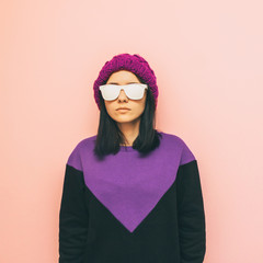Fashionable woman in stylish pose. purple knitted hat and geometric sweater. pastel trend. minimalism.