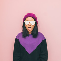 Lovely and crazy girl shows her tongue and standing in a stylish pose. cool oversized sweater in purple and black colors. funky and minimal