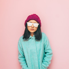 Lady in winter clothing: oversize mint coat and purple hat on pink wall. Fashion of 90's. Pastel and minimalism.