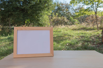 photo Frame on a wooden on wood table in the garden .