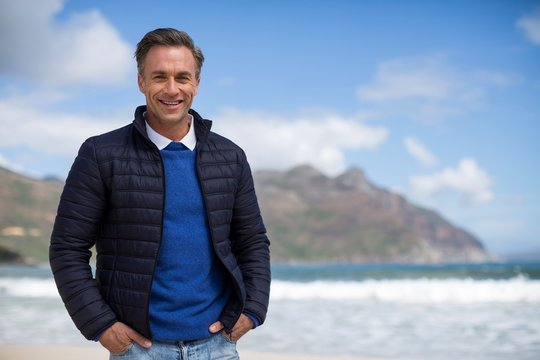 Smiling mature man standing on the beach