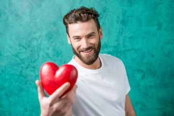 Handsome man in the white t-shirt giving red heart standing on the painted green wall background. Valentine's Day concept