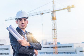 The architect wear white safety helmet and hold the blueprint wi