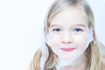Little child blond girl in a bubble bath filled with soap foam