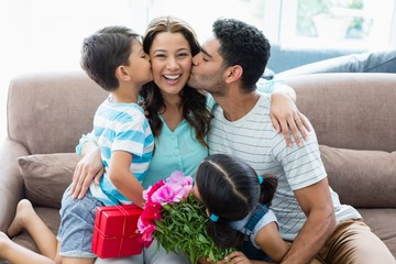 Woman receiving kiss from his husband and kids in living room