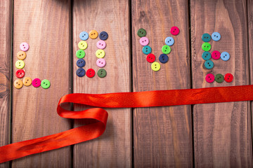 the word love formed from multi-colored buttons decorated with red satin ribbon