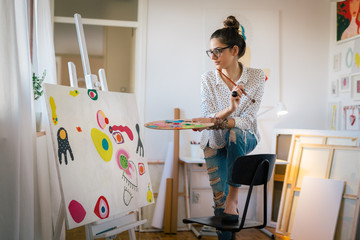 Bringing her creativity to life. Woman painting in her art studio