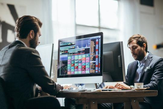 Broker analysing stock market on his computer.