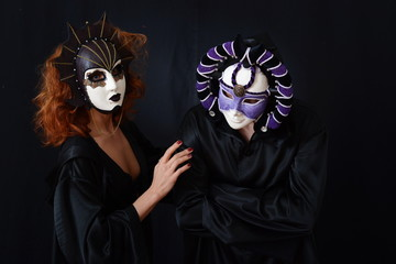 girl in red hair and a guy in an old Venetian masks